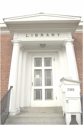 facade of old library building; white columns and portico against red brick with gray cement steps and a large, glass-paned entry door