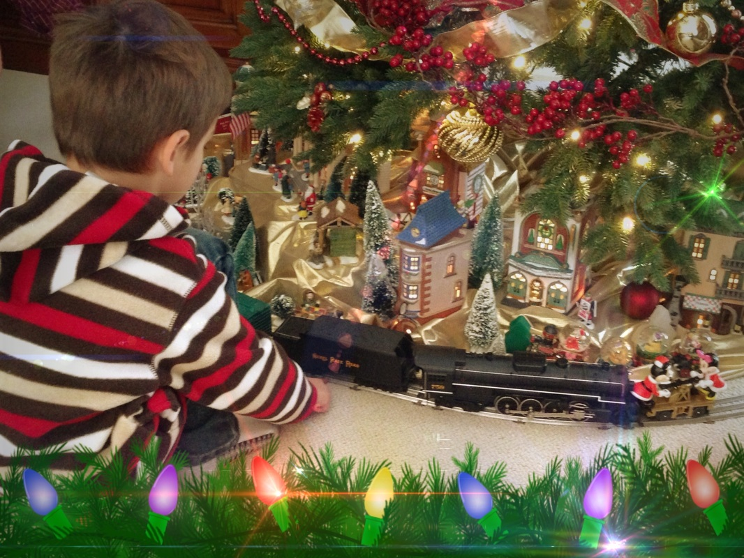 Holiday Traditions Light the Season: little boy watching a toy train run under a Christmas tree