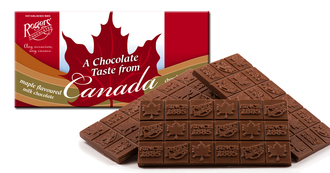 Slabs of Chocolate bars agains white candy box, with red maple leaf and red bars that say a chocolate taste from canada, maple syrup