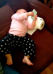 Picture of a toddler totally engaged in the tablet she holds in her hands. catmichaelswriter.com