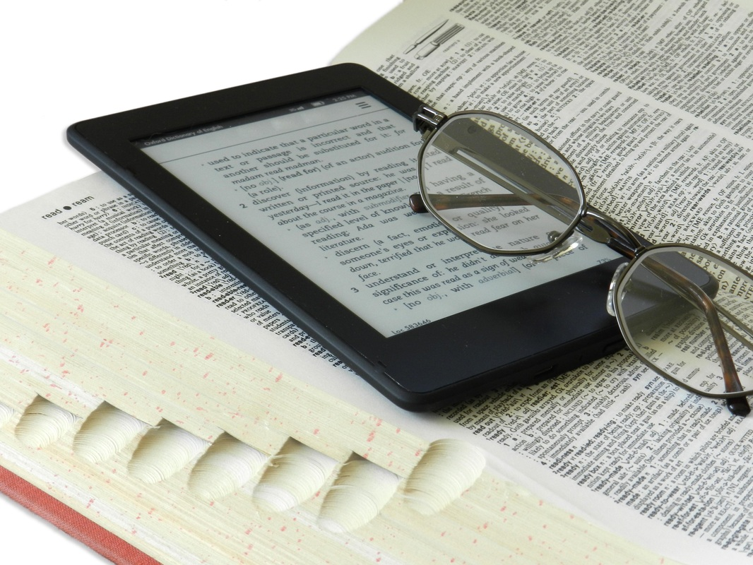 Picture: Ereader sits atop a dictionary with reading glasses_Why You Might Not Want to Toss Your E-reader ~ www.catmichaelswriter.com