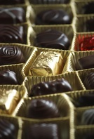 A box of gold-wrapped chocloates in different shapes and sizes